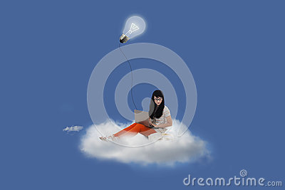 Beautiful female using laptop on cloud under lightbulb