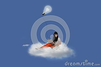 Beautiful female using laptop on cloud under lightbulb