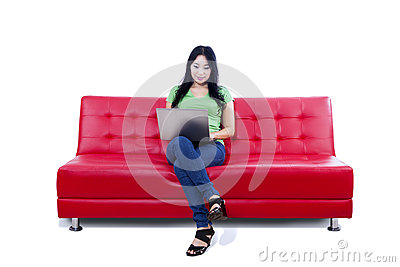 Beautiful female using laptop on red sofa - isolated