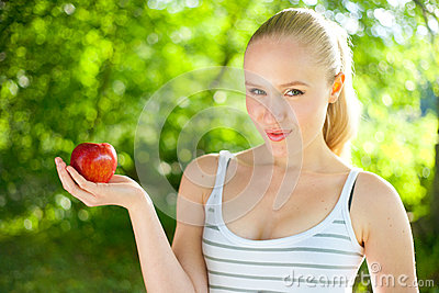 Beautiful fit and healthy woman holding an apple