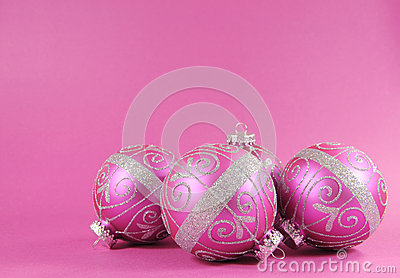 Beautiful fuchsia pink festive bauble ornaments on a feminine pink background with copy space