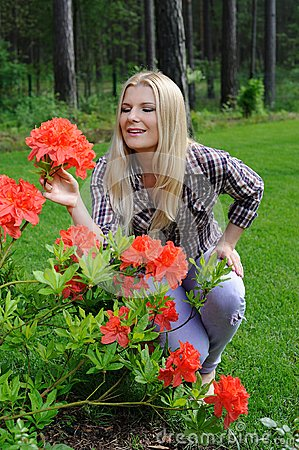 Beautiful gardener woman with red flower bush