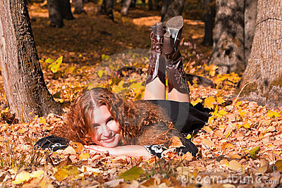 A beautiful ginger-haired woman in fall forest