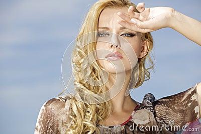 Beautiful girl on background blue sky