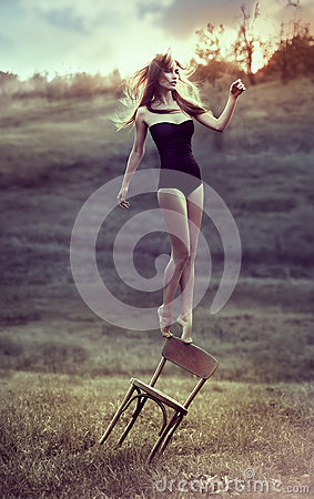Free Beautiful Girl Balances On Back Of Chair Outdoors. Royalty Free Stock Photos - 29634568