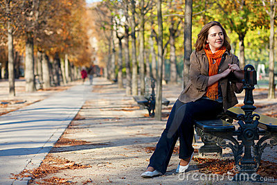 Beautiful girl at the bench by fall