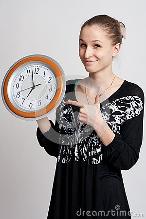 Beautiful girl with a big clock in his hands