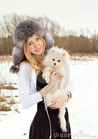 The beautiful girl the blonde in a cap with a dog