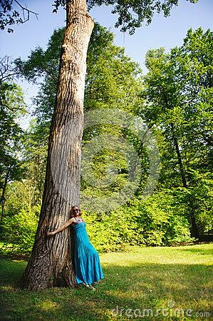Beautiful girl in blue dress near tree
