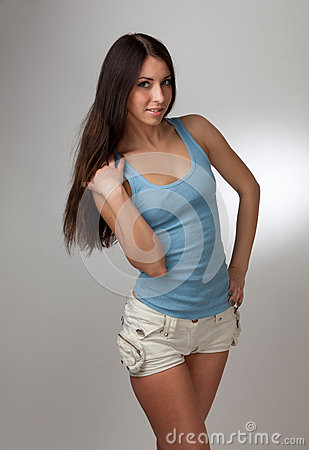 A beautiful girl in a blue t-shirt with a gray bac