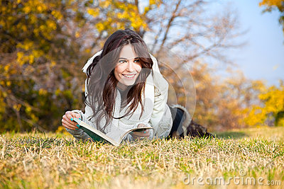 Beautiful girl with book lying on grass