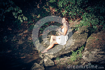 Girl with book onbank of small river