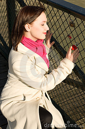 Beautiful girl on a bridge with little red heart