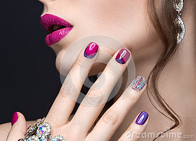 Beautiful girl with a bright evening make-up and pink manicure with rhinestones. Nail design. Beauty face. Stock Photo