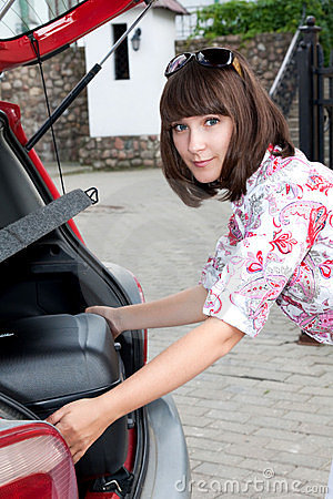 Beautiful girl in a car trunk loads, a big, heavy,