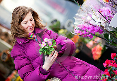 Beautiful girl choosing flowers at market