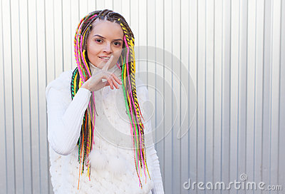 Beautiful girl with colored dreadlocks summer sunny day in a white jacket and lips finger asking for silence Stock Photo