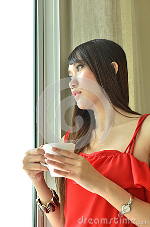 Beautiful girl with cup of coffee looking out