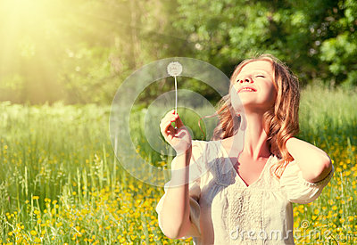 Beautiful girl with dandelion enjoying summer sun