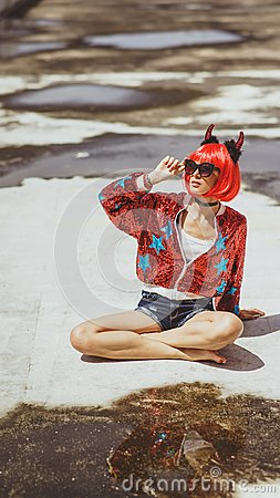 Free Beautiful Girl Devil Sitting On City Background Near The Puddle With His Reflection. In Anticipation Of Halloween Stock Images - 102352214