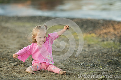 Beautiful girl with Down syndrome shows how a bird flies on the beach Stock Photo