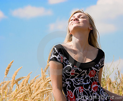 Beautiful girl dreaming over blue sky