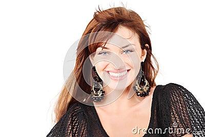 Beautiful girl in dress and bid earrings smiles