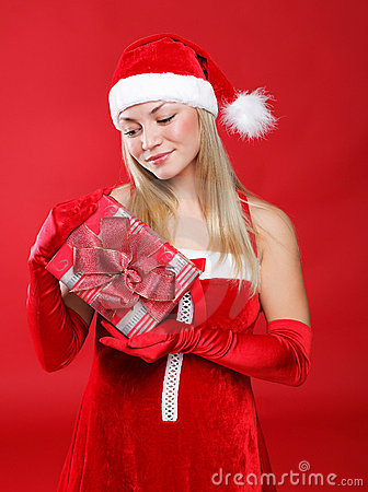 Beautiful girl dressed as Santa holds a gift.