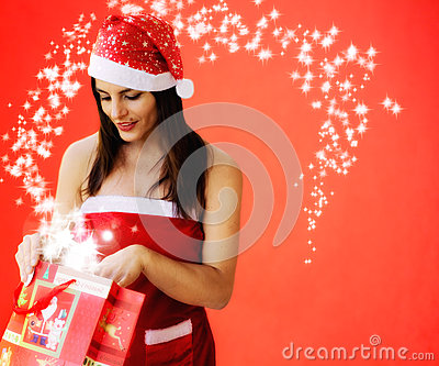 Beautiful girl dressed santa claus opens a  gift
