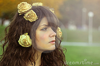 Beautiful girl with dry roses in her curly hair