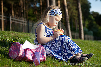 Beautiful girl eating muffin is on green grass. Stock Photo