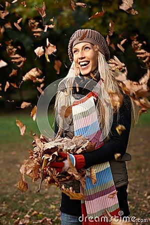 Beautiful girl enjoying autumn in park laughing