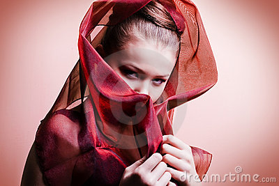Beautiful girl enveloped  in red headscarf