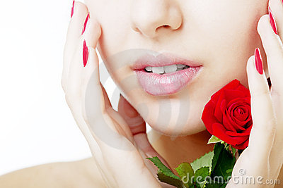 Beautiful girl face close up with a rose in hand