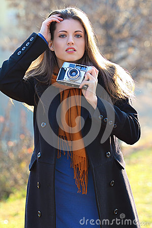 Beautiful girl in fashion pose with old camera in hand