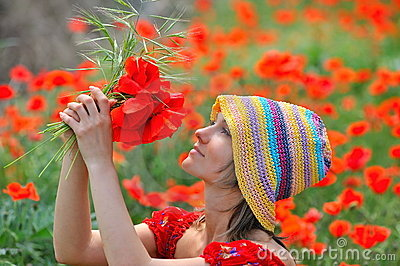Beautiful girl on a field with poppies