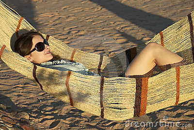 Beautiful girl in glasses is laying in hammock