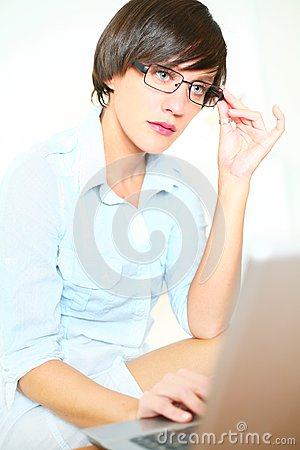 Beautiful girl with glasses working on laptop