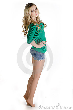 Beautiful girl in a green shirt standing on toes