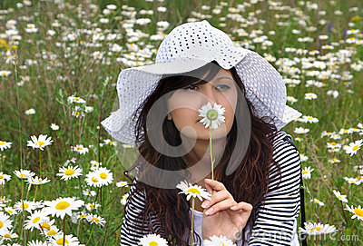 Beautiful girl in hat with camomile