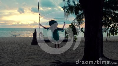 Beautiful girl in a hat at sunset swinging on a swing on a seashore. Silhouette pretty young woman sitting on a hanging stock video