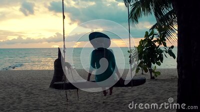 Beautiful girl in a hat at sunset swinging on a swing on a seashore. Silhouette pretty young woman sitting on a hanging stock video footage