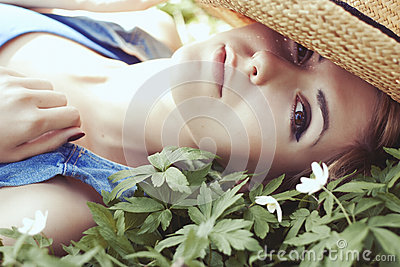 Beautiful girl in hat with white spring flowers