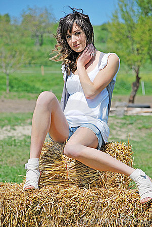 Beautiful girl on a hay bale