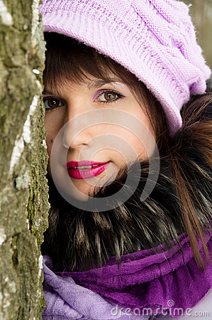 Beautiful girl hiding behind the tree