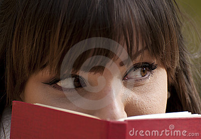 Beautiful girl hiding herself behind a book