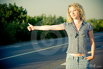Beautiful girl hitchhiking on the road