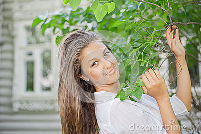 Beautiful girl hold for branch with leaves