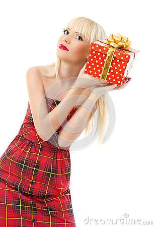 Beautiful girl holding christmas gift in red dress