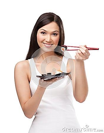 Beautiful girl holding sushi with a chopsticks